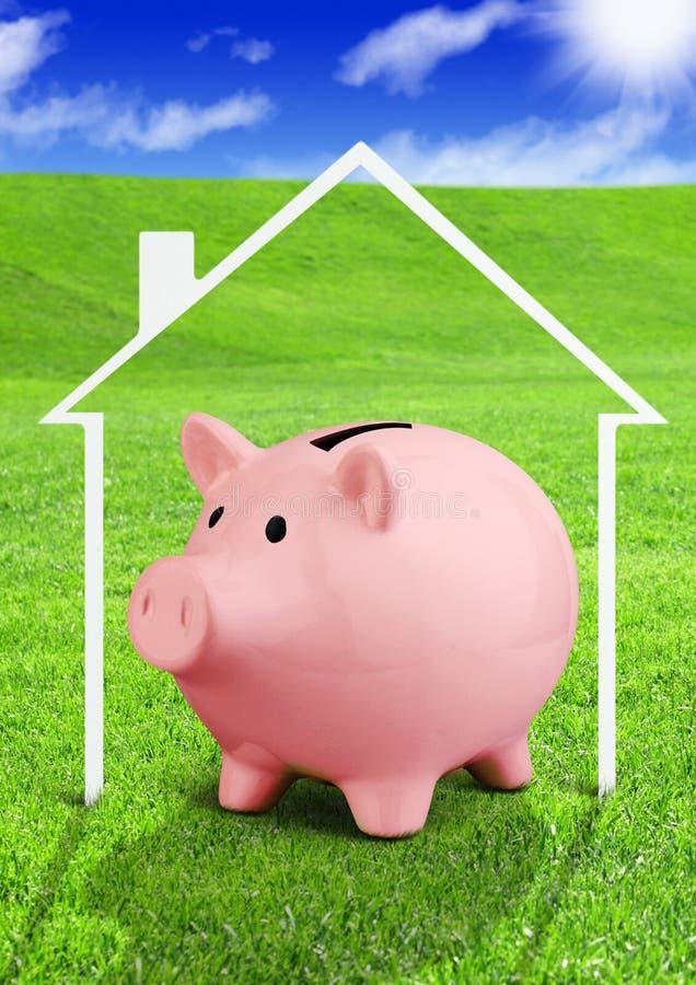 Besparingar för ett husbegrepp, spargris på fält arkivfoton