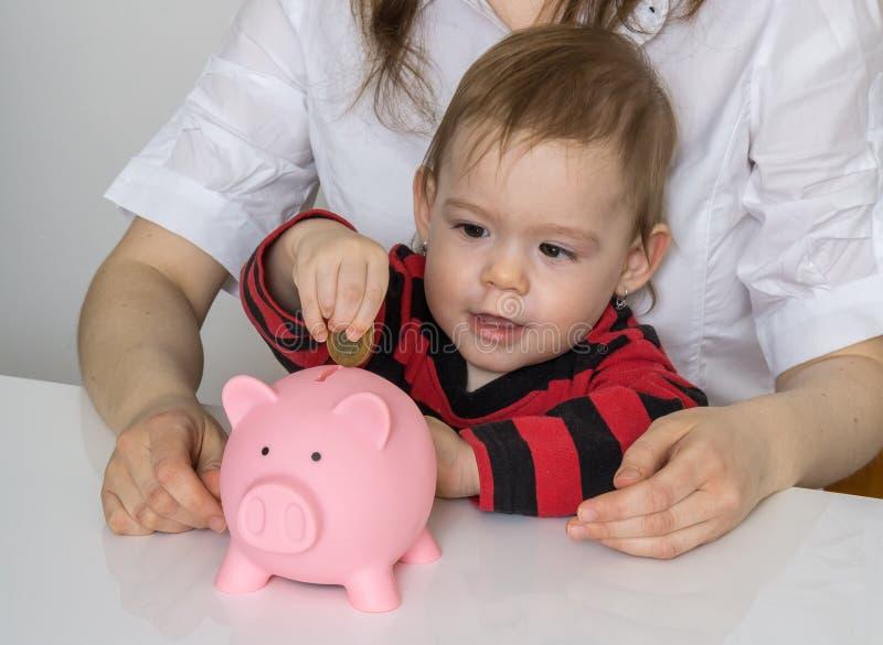 Besparingar för framtid Lilla flickan sätter mynt i den piggy pengarbanken royaltyfria bilder