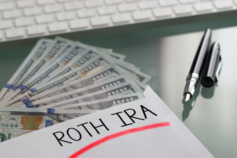 Besparingar f?r avg?ngbegrepp med Roth Ira som ?r skriftlig p? det vita kuvertet med kassaUS dollar royaltyfri foto