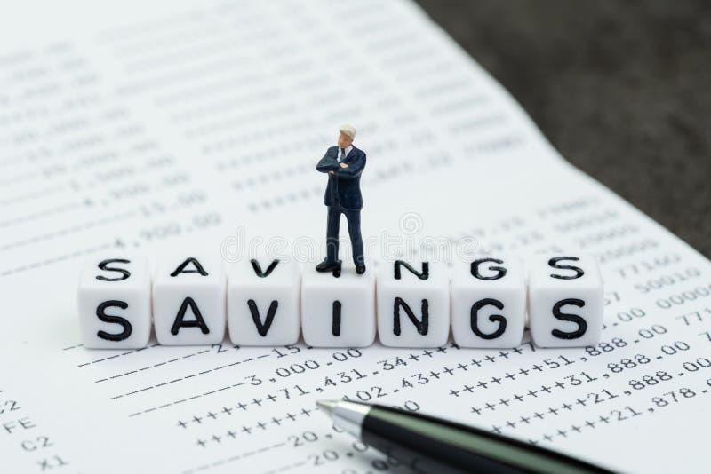 Besparingar finans- eller packa ihopbegrepp, framgångaffärsmanminiatyrdiagram anseende på kubkvarteret med alfabet som bygger ord arkivbilder