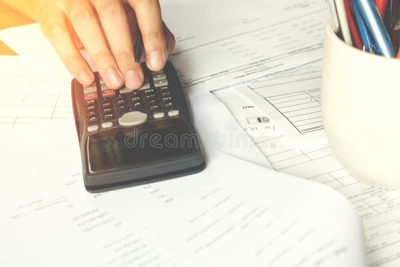 Besparingar, finanser, ekonomi och kontorsbegrepp Affärsfolk som räknar på räknemaskinen royaltyfri fotografi