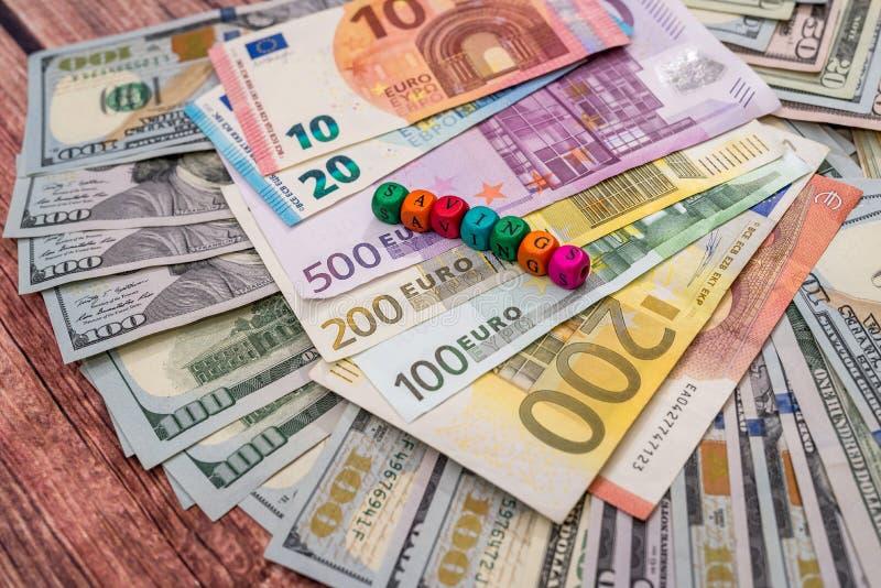 Besparingar uttrycker i träkuber med euro och dollaren fotografering för bildbyråer