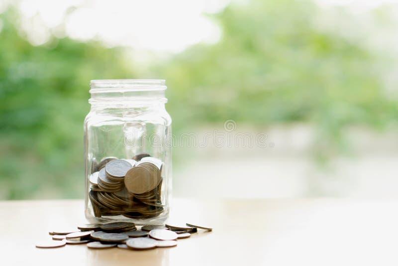 Besparingar uttrycker med pengarmyntet i den glass kruset finansiellt arkivbild