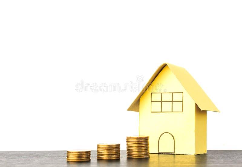 Besparingbegrepp: Pappers- hus med myntet på trä royaltyfri foto