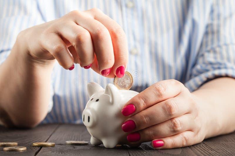 Besparingbegrepp, vit spargris med den mänskliga kvinnliga handen som inom sätter in myntet royaltyfri bild