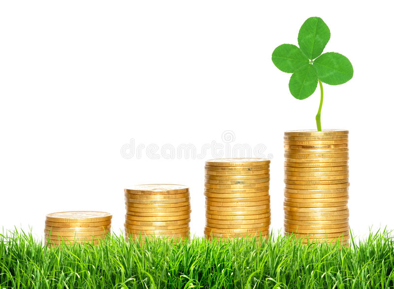 Besparingen, stijgende kolommen van gouden muntstukken en groen klaverblad royalty-vrije stock afbeeldingen