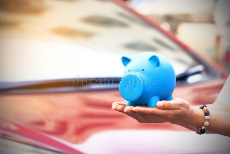 Besparingsgeld en leningen voor autoconcept, Jonge vrouw die blauw spaarvarken met status houden bij de achtergrond van het autop stock foto's