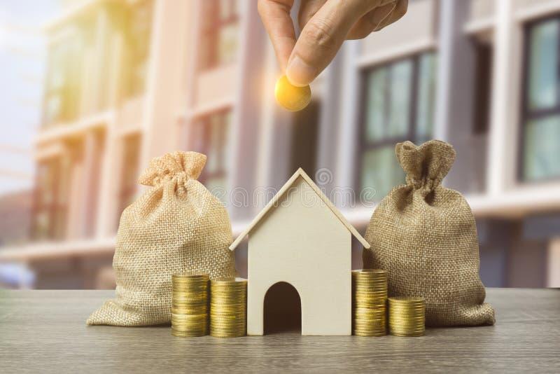 Besparingsgeld, huislening, hypotheek, een bezitsinvestering voor toekomstig concept Een mensenhand die geldmuntstuk over kleine  royalty-vrije stock foto's