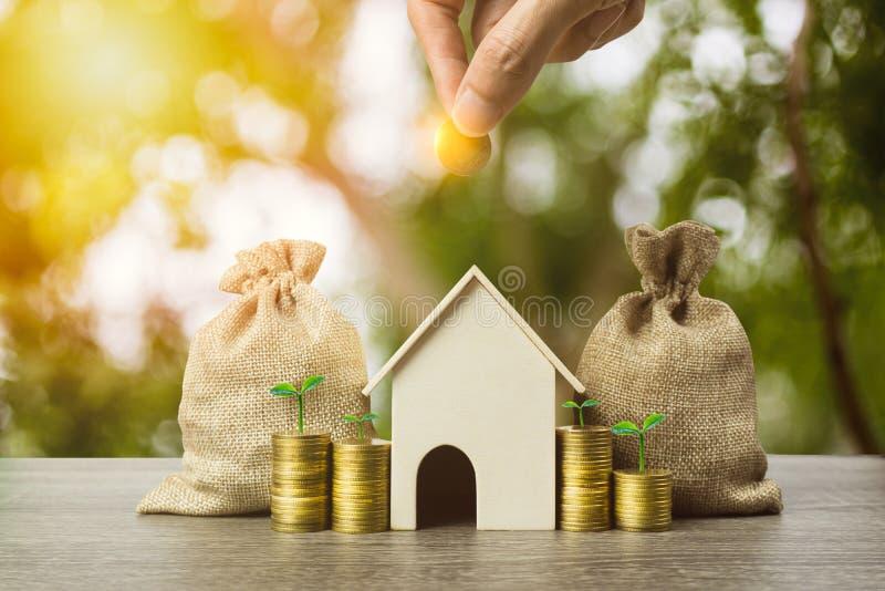 Besparingsgeld, huislening, hypotheek, een bezitsinvestering voor toekomstig concept Een mensenhand die geldmuntstuk over kleine  royalty-vrije stock afbeelding
