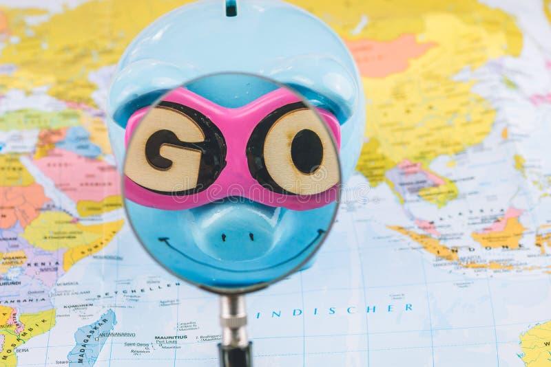 Besparingspargris med solglasögon Förstoringsapparatzoome in i GÅR slogan Svinet blir på världskartan som är klar för lopp arkivbild