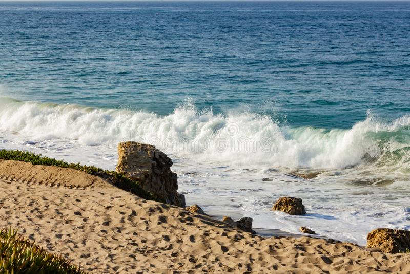Bespattende golf op terugslag en zandig strand, met grote keien, zand stock afbeelding
