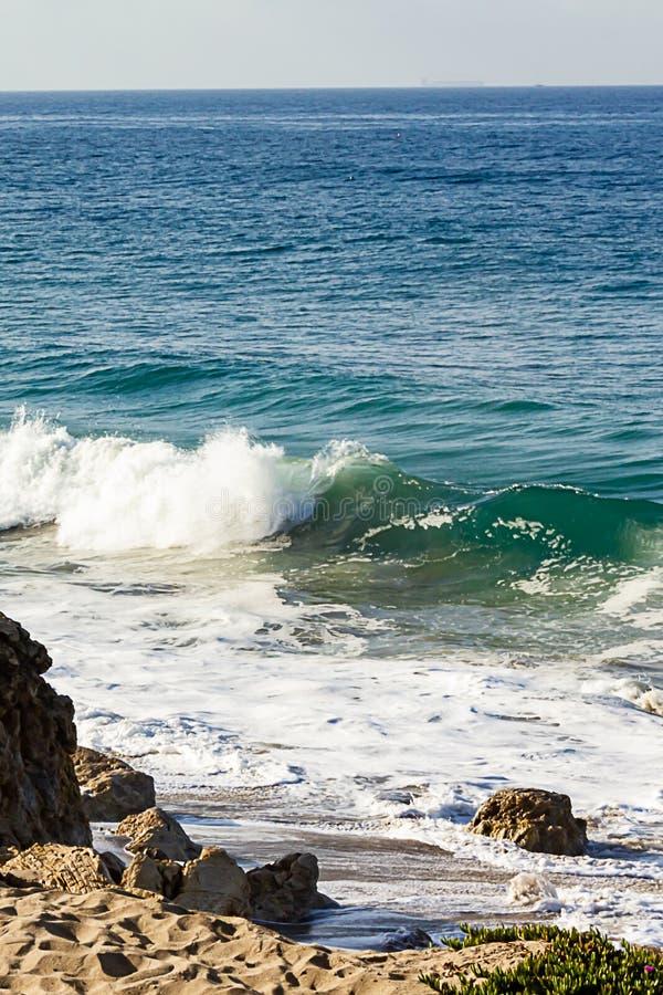 Bespattende golf op terugslag en zandig strand, met keien en zand, stock afbeeldingen
