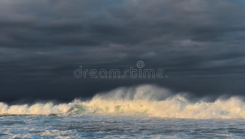 Bespattende golf tegen een stormachtige hemel Het krachtige oceaangolf breken royalty-vrije stock afbeelding