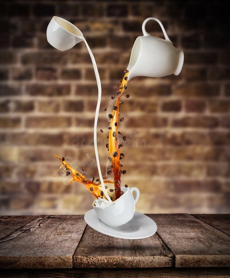 Bespattende vloeistof van koffie en melk in witte kop op houten lijst royalty-vrije stock foto