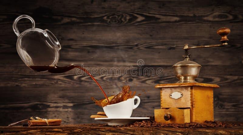 Bespattende vloeistof van koffie van kruik in kop op houten lijst royalty-vrije stock foto