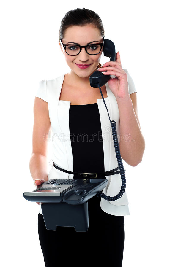 Bespectacles secretary answering a call. Charming young corporate employee communicating on telephone royalty free stock photography
