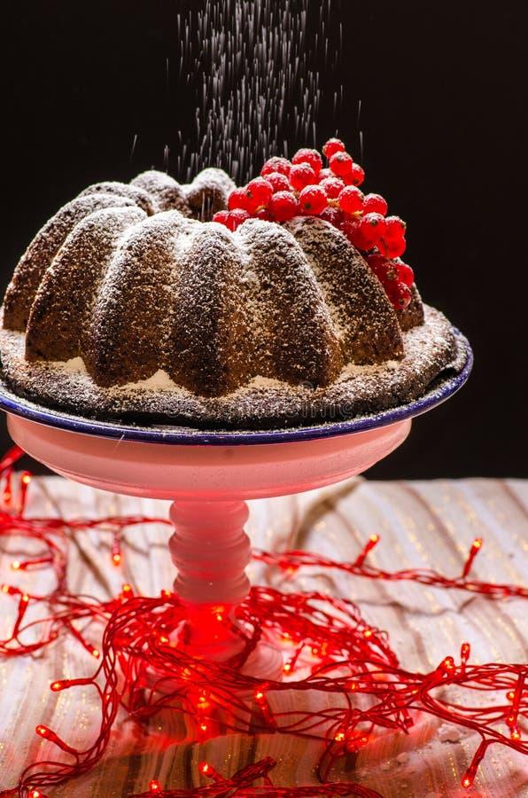 Besprühen des Zuckers auf Kuchen stockfoto