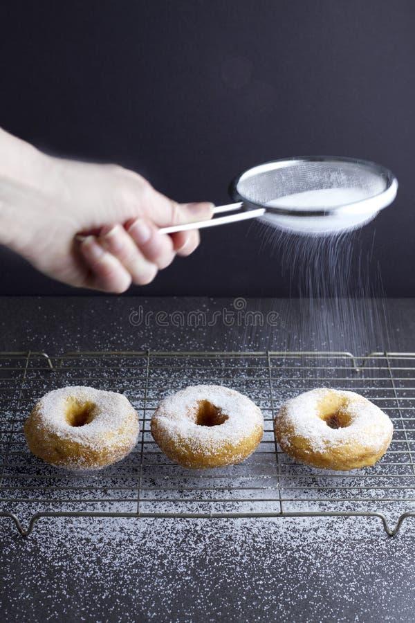 Besprühen des Zuckers auf 3 Ringdonuts lizenzfreie stockfotografie