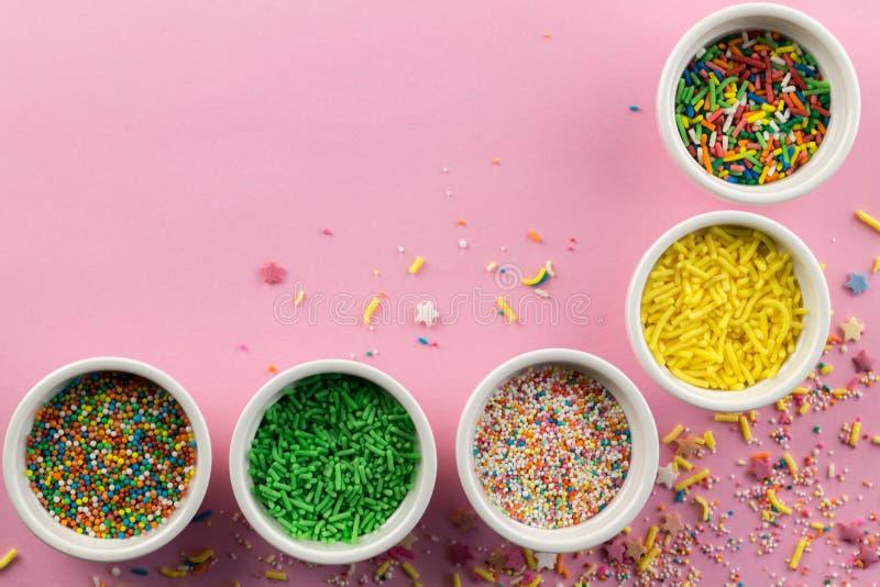 Besprüht auf rosa Hintergrund - sortierte bunten Kuchenbelag besprüht in den kleinen weißen Schüsseln auf rosa - Draufsicht lizenzfreie stockfotografie