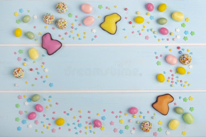 Besprüht bunte Schokoladenhäschen, -bonbons und -helles Ostern lizenzfreie stockfotos