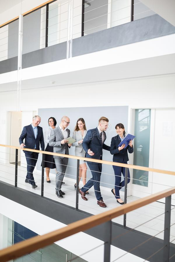 Besprechende Geschäftsleute beim Gehen auf Korridor im Büro lizenzfreie stockbilder