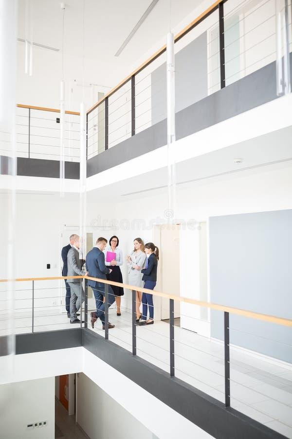 Besprechende Kollegen bei der Stellung in der Ecke des Korridors im Büro stockbild