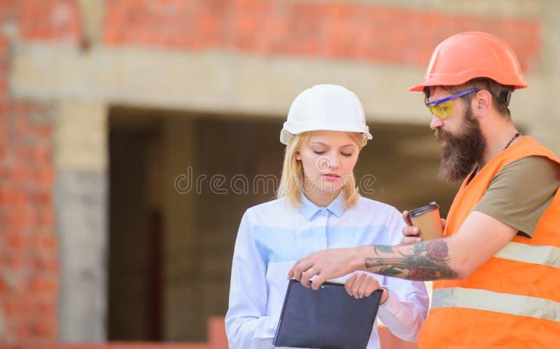 Bespreek vooruitgangsplan De de vrouweningenieur en bouwer delen bouwwerf mee Communicatie van het bouwteam concept royalty-vrije stock foto's