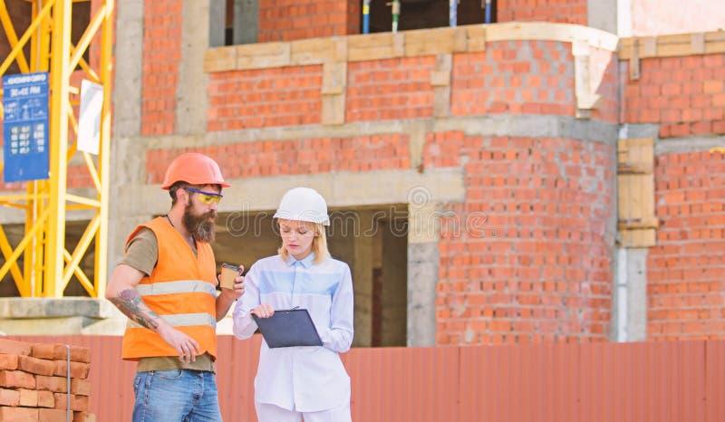 Bespreek vooruitgangsplan De de vrouweningenieur en bouwer delen bouwwerf mee Verband tussen bouw royalty-vrije stock foto's