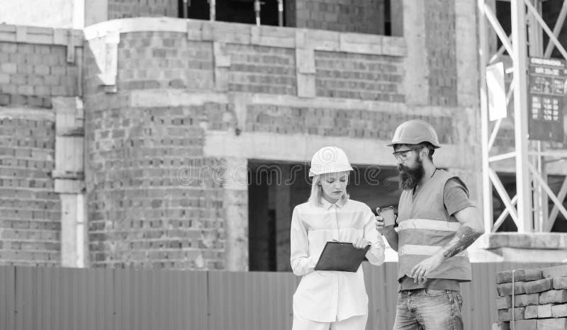 Bespreek vooruitgangsplan De de vrouweningenieur en bouwer delen bouwwerf mee Verband tussen bouw royalty-vrije stock fotografie