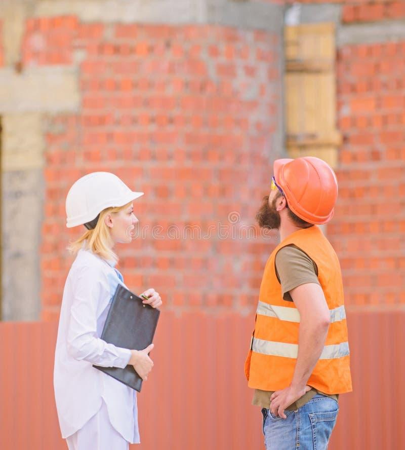 Bespreek vooruitgangsplan huis pictogram dat van sleutels, op bakstenen muurachtergrond wordt gemaakt De cli?nt en de deelnemers  stock foto