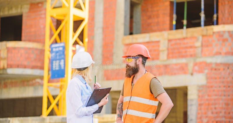 Bespreek vooruitgangsproject Het concept van de veiligheidsinspecteur De inspecteur en de gebaarde brutale bouwer bespreken bouwv royalty-vrije stock afbeeldingen