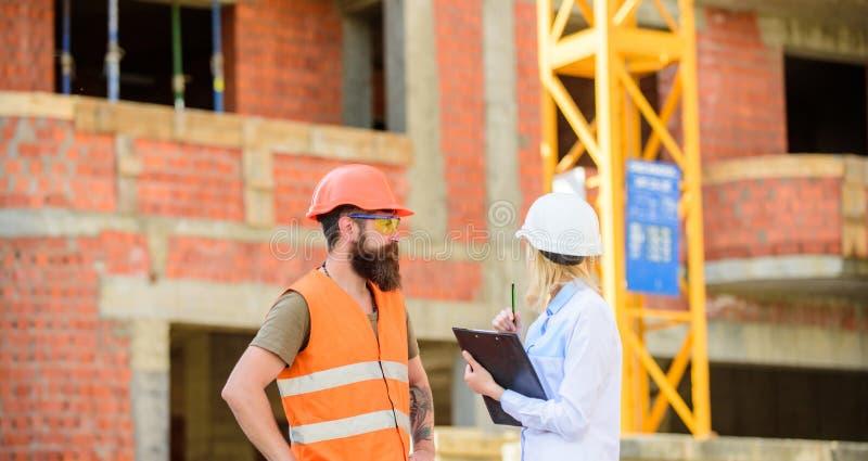 Bespreek vooruitgangsproject Het concept van de veiligheidsinspecteur De inspecteur en de gebaarde brutale bouwer bespreken bouwv royalty-vrije stock afbeelding