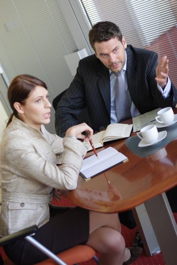 Bespreking, bedrijfsman en vrouw die in het bureau spreken royalty-vrije stock afbeeldingen