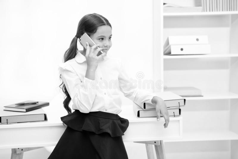 Besprekingsconcept Gelukkige meisjesbespreking op mobiele telefoon Weinig smartphone van het kindgebruik in school Bespreking op  royalty-vrije stock fotografie