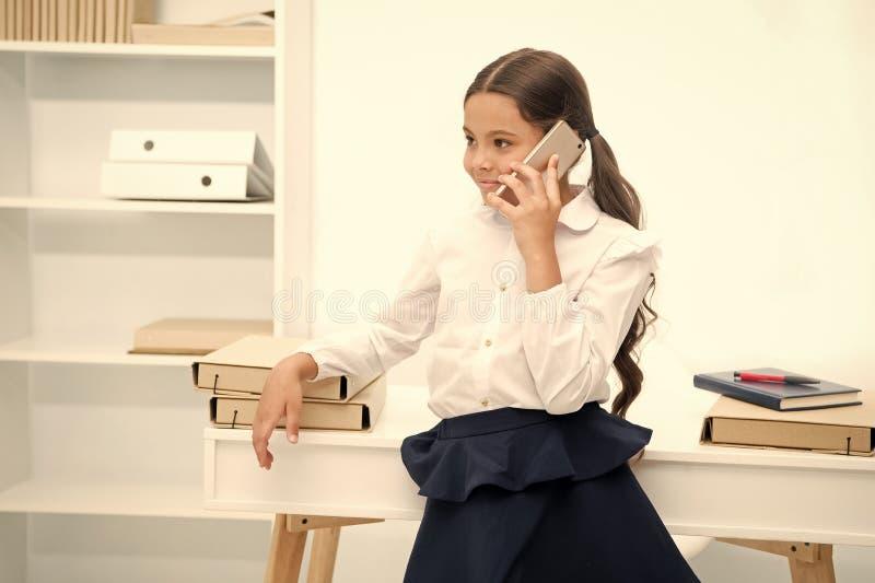 Besprekingsconcept Gelukkige meisjesbespreking op mobiele telefoon Weinig smartphone van het kindgebruik in school Bespreking op  stock afbeelding