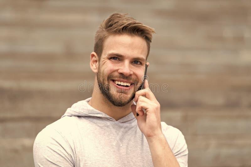 Besprekingsconcept Gelukkige mensenbespreking op mobiele telefoon Jonge smartphone van het kerelgebruik om openlucht te spreken O stock fotografie