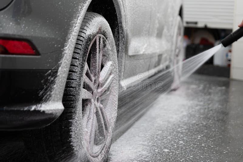Bespuitende de autowiel en band van de autowasserettearbeider met wit actief schoonmakend schuim stock fotografie