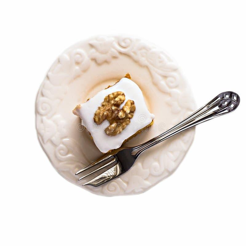Bessern Sie den Walnusskarottenkuchen und -gabel aus, die auf weißem Hintergrund lokalisiert werden stockfoto
