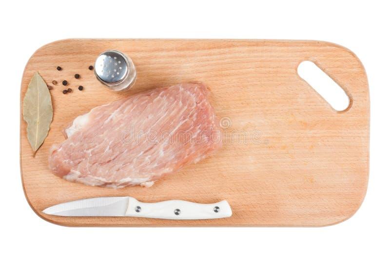 Bessern Sie rohes Schweinefleisch, Messergewürze auf lokalisiertem Weiß des hölzernen Brettes aus lizenzfreie stockfotos