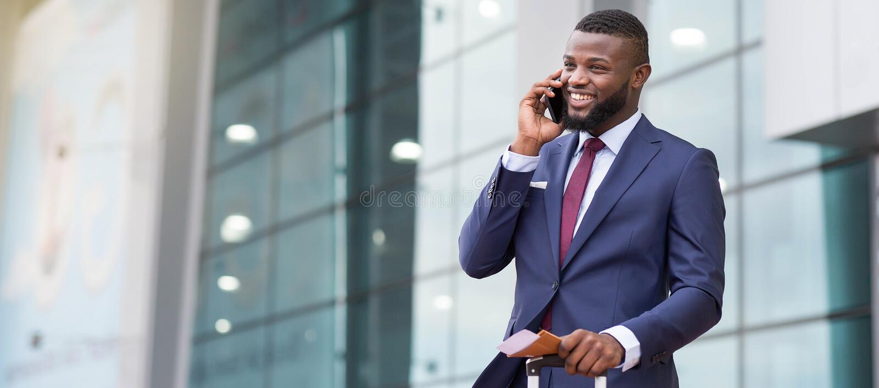 Beställa en taxi Afrikansk affärsman som ankommer till flygplatsen och talar på telefonen royaltyfri foto