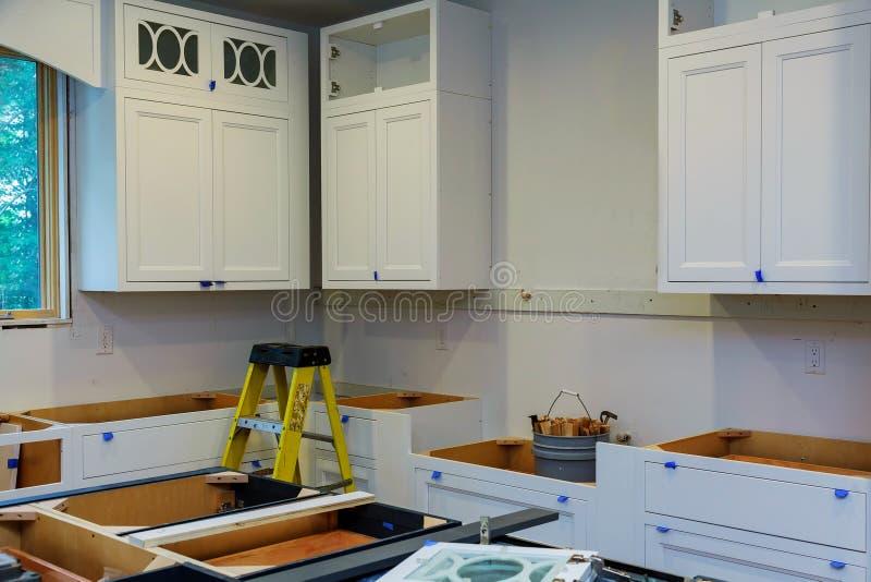 Beställnings- köksskåp i olika etapper av installationsgrunden för ön i mitt royaltyfria foton