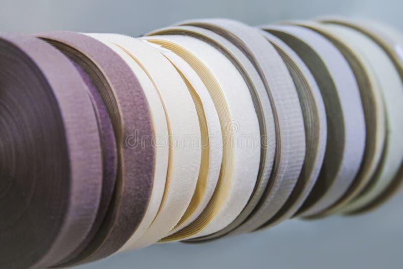 Beståndsdelar av sömnaden, textilband, gummiband, hoprullade pastellfärgade färger arkivfoton