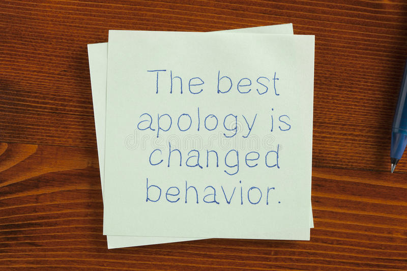 The best apology is changed behavior written on note. Top view of the best apology is changed behavior written note on the wooden desk royalty free stock image