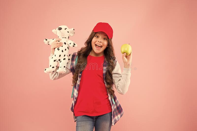 Best apple snack. Happy little child have snack break on pink background. Small girl smile with puppy toy and apple. Healthy organic snack. Snack that gives royalty free stock photo