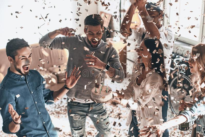 Best birthday party! Top view of happy young man celebrating birthday among friends while standing in room with confetti flying royalty free stock images
