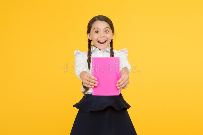Best book. small girl in school uniform. reading story. childrens literature. kid learning grammar. back to school. Dictionary notebook. Get information stock image