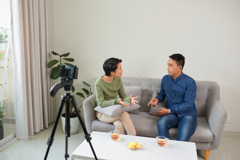 Best business vlog. Young woman and man talking while making new video indoors stock photo
