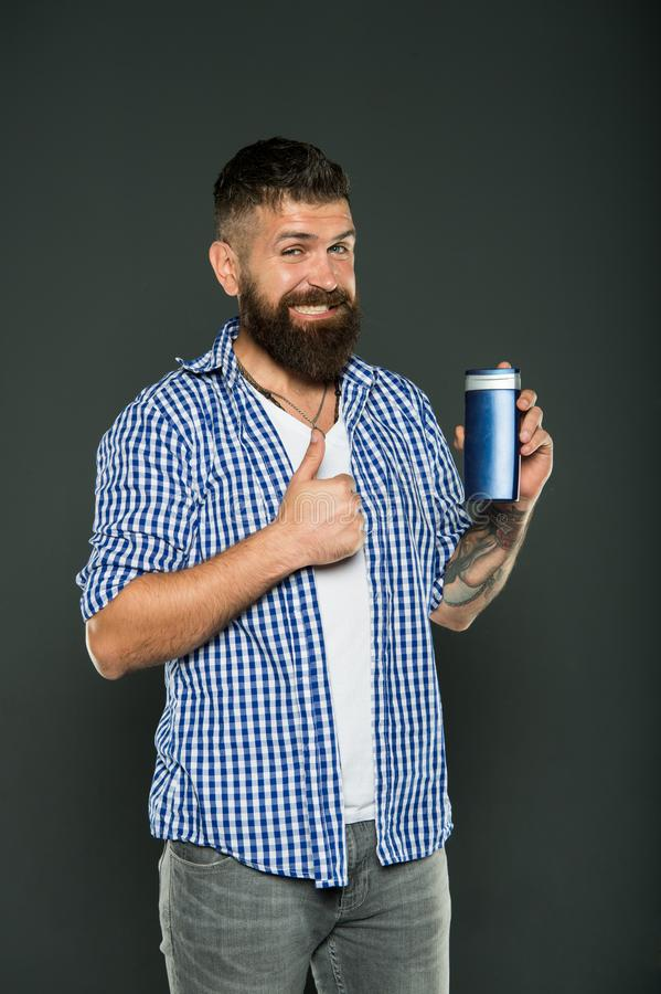 The best care ever. Bearded man showing thumbs up for hair care product on grey background. Happy hipster liking his. Shampoo or gel for personal care. Skin and royalty free stock photos