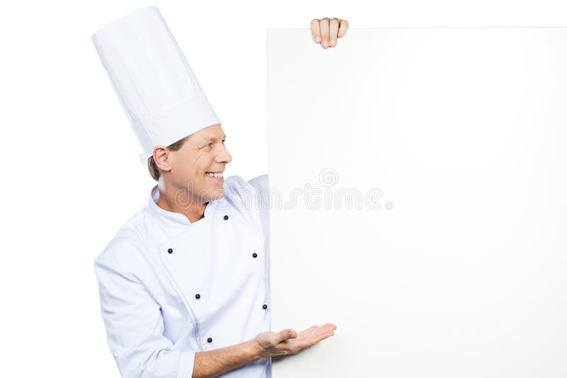 The best from chef. Confident mature chef in white uniform leaning at the copy space and pointing it while standing against white background royalty free stock image