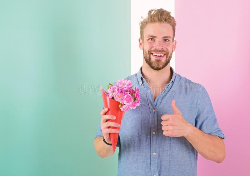 Best choice. Man ready for date bring pink flowers. Boyfriend smiling holds bouquet waiting for date. Guy bring romantic. Pleasant gift waiting for her. Macho royalty free stock photography